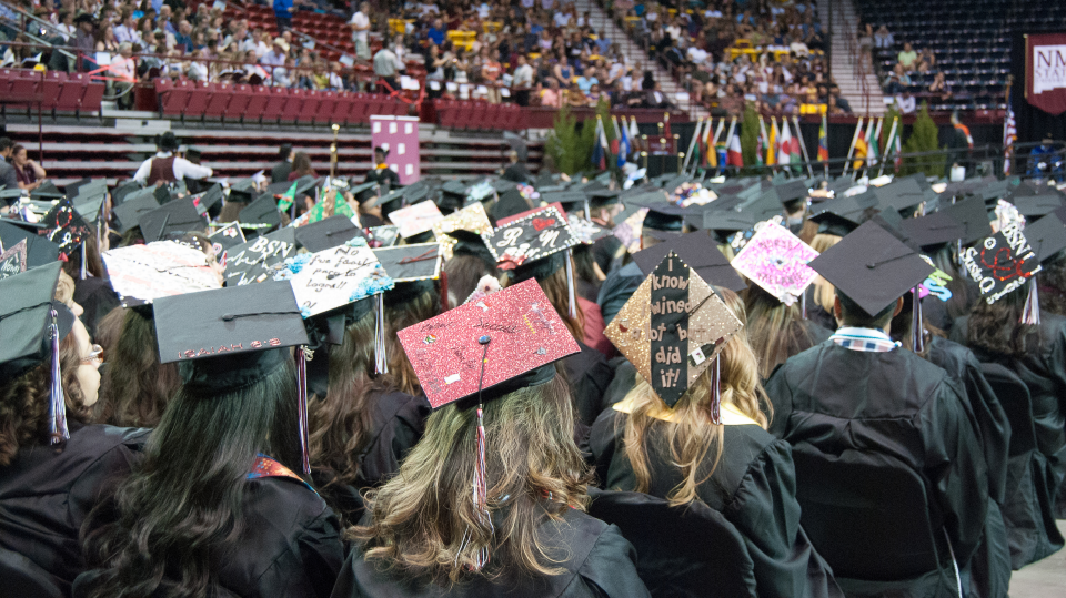 Graduates with decorated caps wait for their name to be called at Commencement.